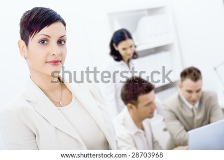 Businesswoman standing in front looking at camera, smiling. Three business colleagues working on laptop computer in background. - stock photo