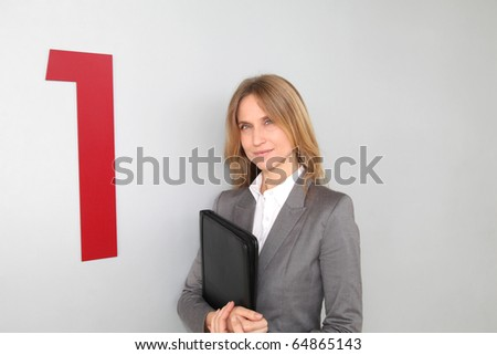 Businesswoman standing in hall against wall - stock photo