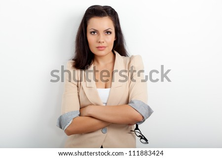 businesswoman standing near wall and holding eyeglasses - stock photo