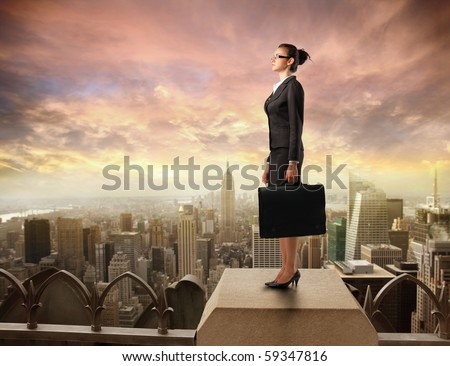 Businesswoman standing on the rooftop of a skyscraper