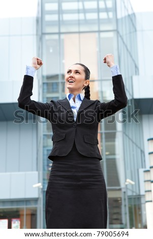 businesswoman standing outdoor  celebrating her winning, front office bulding
