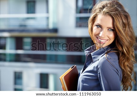 Businesswoman standing outside a modern house #111963050