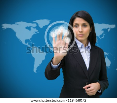 Businesswoman standing touching holographic screen against blue world map background