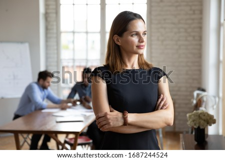 Businesswoman standing with arms crossed looks in window daydreaming about career growth, plan future deal feels confident. Promoted employee, head position independent woman, company owner concept