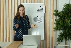 Businesswoman standing writing on a blackboard and making a video call. Woman coach coach teachers students company employees remote online webcam