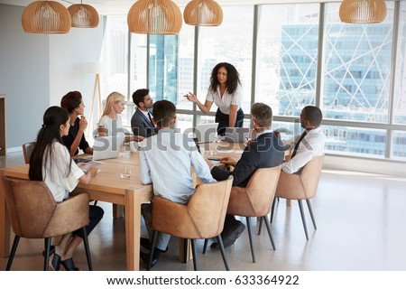 Businesswoman Stands To Address Meeting Around Board Table
