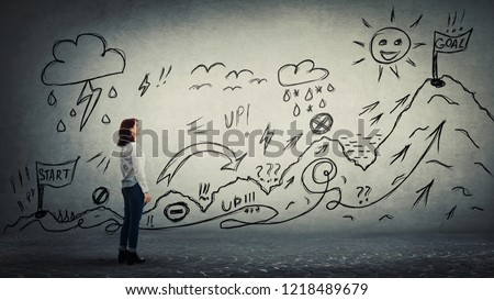 Businesswoman starting a life quest with obstacles drawn on wall. Self overcome climbing mountain with ups and downs for reaching goals. Difficult road to finish flag. Career move metaphor.