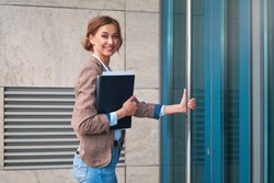 Businesswoman successful woman business person standing outdoor corporate building exterior Elegance pretty caucasian professional middle age female Bank worker enter building open door and smiling