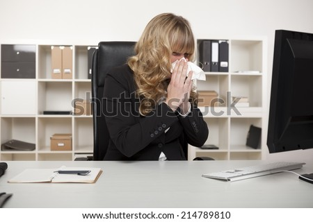 Businesswoman suffering from a cold or hay fever blowing her nose at her desk with a tissue as she continues reading the screen of her computer