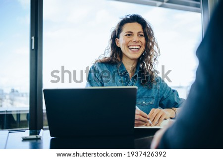 Businesswoman taking interview of a job applicant in office boardroom. Smiling recruiter asking questions to a male candidate during job interview.