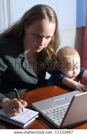 Businesswoman taking notes from a laptop while her son sits with her.