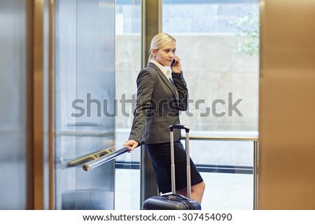 Businesswoman talking on the phone in elevator