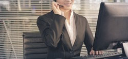 businesswoman talking using headset while working on her computer at the office