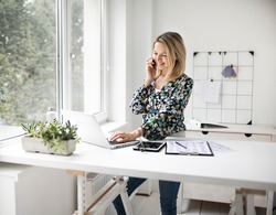 Businesswoman telephoning using cellphone while working at ergonomic standing desk.