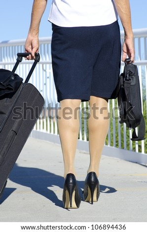Businesswoman traveling with suitcase and laptop, wearing white blouse, dark skirt and high heel shoes.