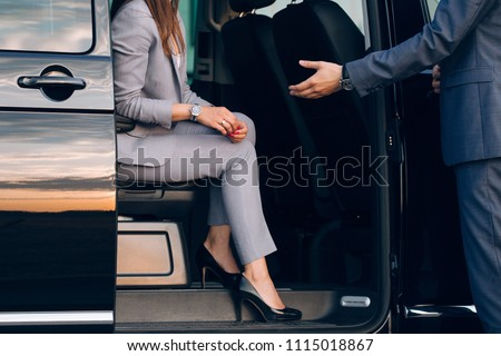Businesswoman travelling in vip car transfer. Driver helping woman to get outside the car