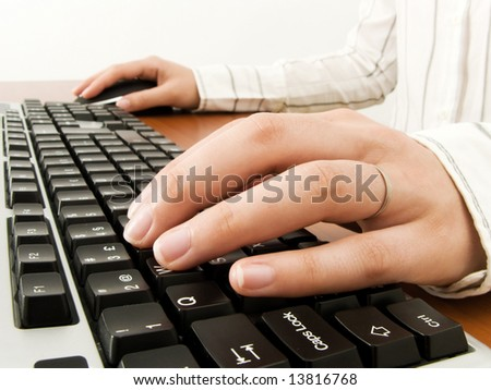 Businesswoman typing in the computer keyboard and using a mouse