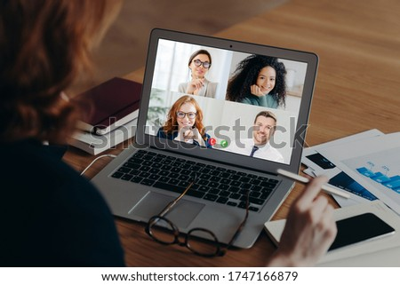 Businesswoman uses laptop application for communication with several people, has vitrual conference, works freelance from home, sits at desktop, surrounded with paper documents. Online negotiations