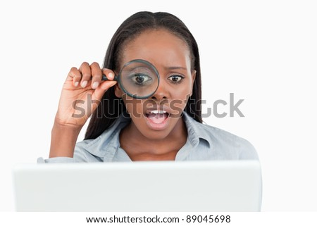 Businesswoman using a magnifying glass to look at her notebook against a white background