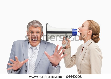 Businesswoman using a megaphone after her colleague against white background