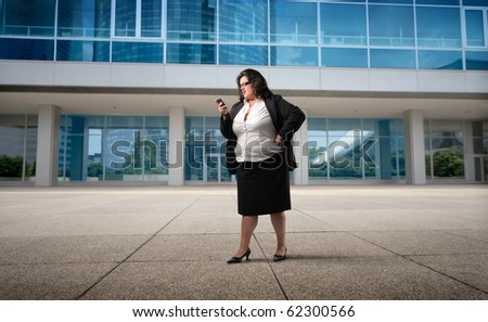 Businesswoman using a mobile in front of an office building
