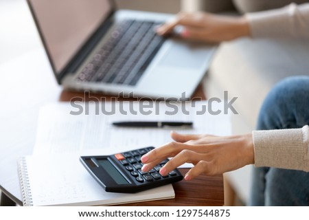 Businesswoman using calculator and laptop for budget cost money management strategy, female hands calculating bills finances expenses taxes doing paperwork at work desk, bookkeeping concept, close up #1297544875