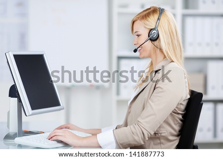 businesswoman using headset working on computer at business desk
