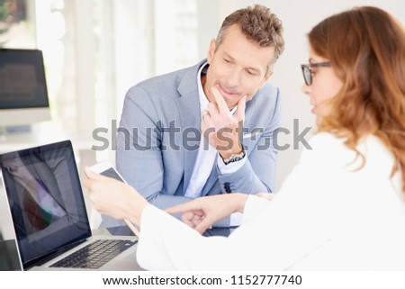 Businesswoman using her digital tablet while sitting at office desk with her thinking colleague and having discussion. Teamwork at the office.