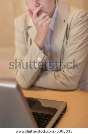 Businesswoman using her laptop on the table with her hand on her chin while pondering