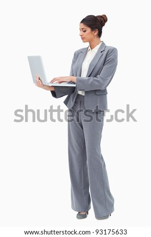 Businesswoman using laptop while standing against a white background