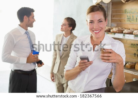 Businesswoman using mobile phone with colleagues behind in office cafeteria