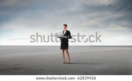 Businesswoman using on a laptop in a desert
