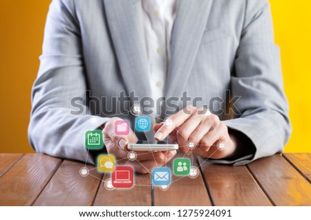 Businesswoman using smart phone. Communication concept, application icons flying around #1275924091