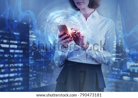 Businesswoman using smartphone with creative abstract business hologram on blurry night city background. Technology and future concept. Double exposure