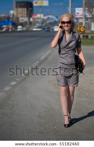 Businesswoman walking to the street and talking to phone