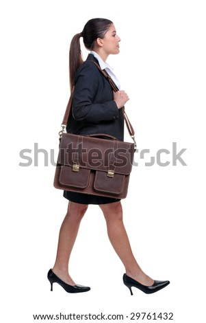 Businesswoman walking with briefcase over her shoulder, isolated on white background.