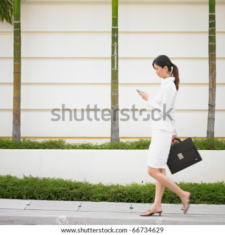 Businesswoman walking with cell phone and briefcase