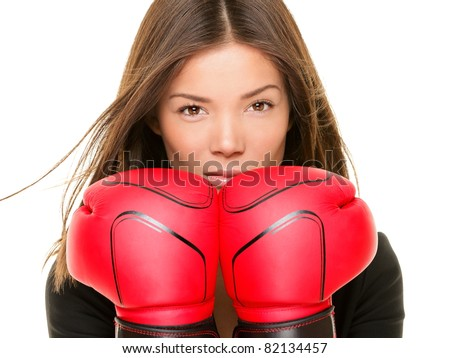 Businesswoman wearing boxing gloves ready to fight. Strength, power or competition concept image of beautiful young mixed race Chinese Asian / Caucasian business woman isolated on white background.