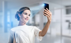 Businesswoman wearing casual t-shirt is checking her personal data. Scanning her face by smart phone to unlock it. Digital connections. Concept of data protection. Blurred office on background
