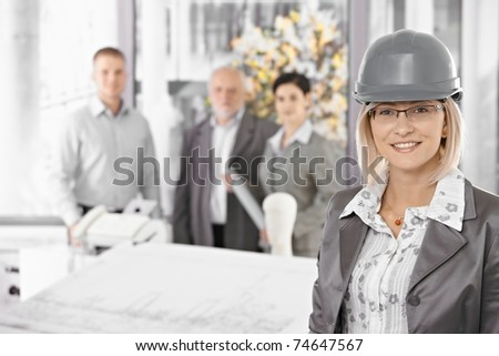 Businesswoman wearing hardhat in architectural office, team standing in background.?