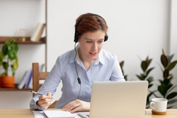 Businesswoman wearing headphones watching video webinar making conference online call writing notes talking, focused woman study online looking at laptop listening translating lecture course