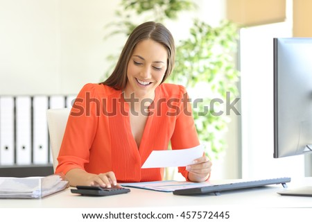 Businesswoman wearing orange blouse doing accounting and calculating with a calculator in a desktop at office