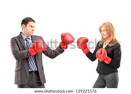Businesswoman with boxing gloves having a fight with a young businessman isolated on white background