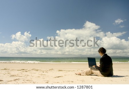Businesswoman with business suit working on the beach
