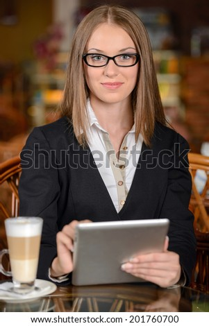 Businesswoman with digital tablet. Beautiful young woman in formalwear working on digital tablet while sitting at the restaurant