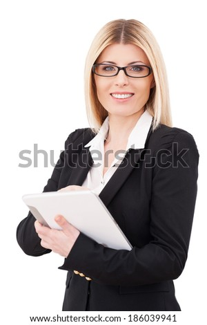 Businesswoman with digital tablet. Confident mature businesswoman working on digital tablet and smiling while standing isolated on white