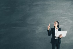 Businesswoman with document in hand and blank blackboard. Business and success concept.
