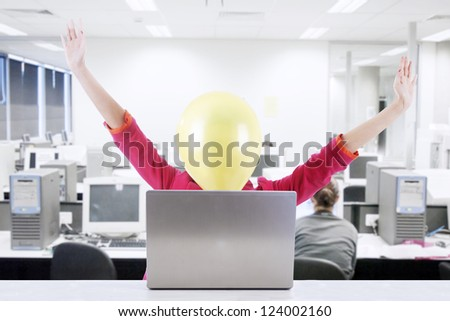 Businesswoman with face covered with balloon expressing happiness. Shot at office