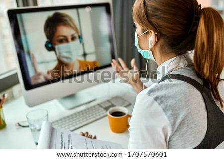 Businesswoman with face mask communicating with her colleague via video call while working in the office during COVID-19 pandemic.