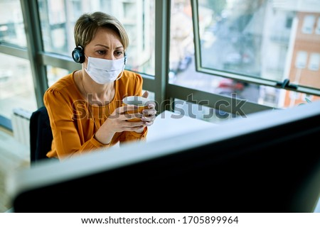 Businesswoman with face mask holding a cup of coffee while reading problematic e-mail on desktop PC in the office.